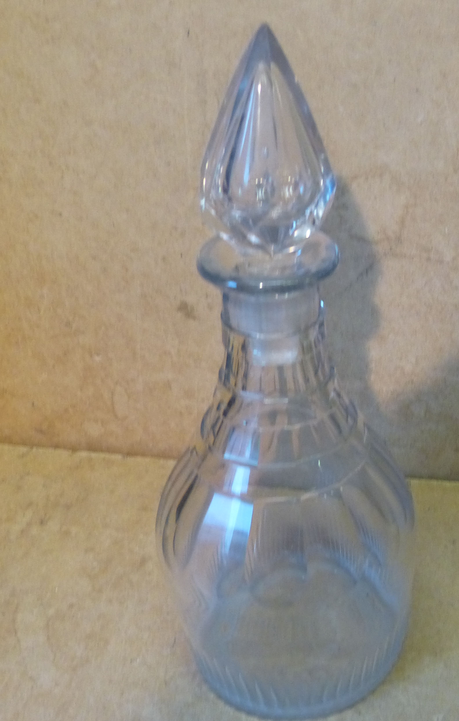A Georgian Cut Glass Round Thin Neck Decanter with stopper, having thumb pattern decoration