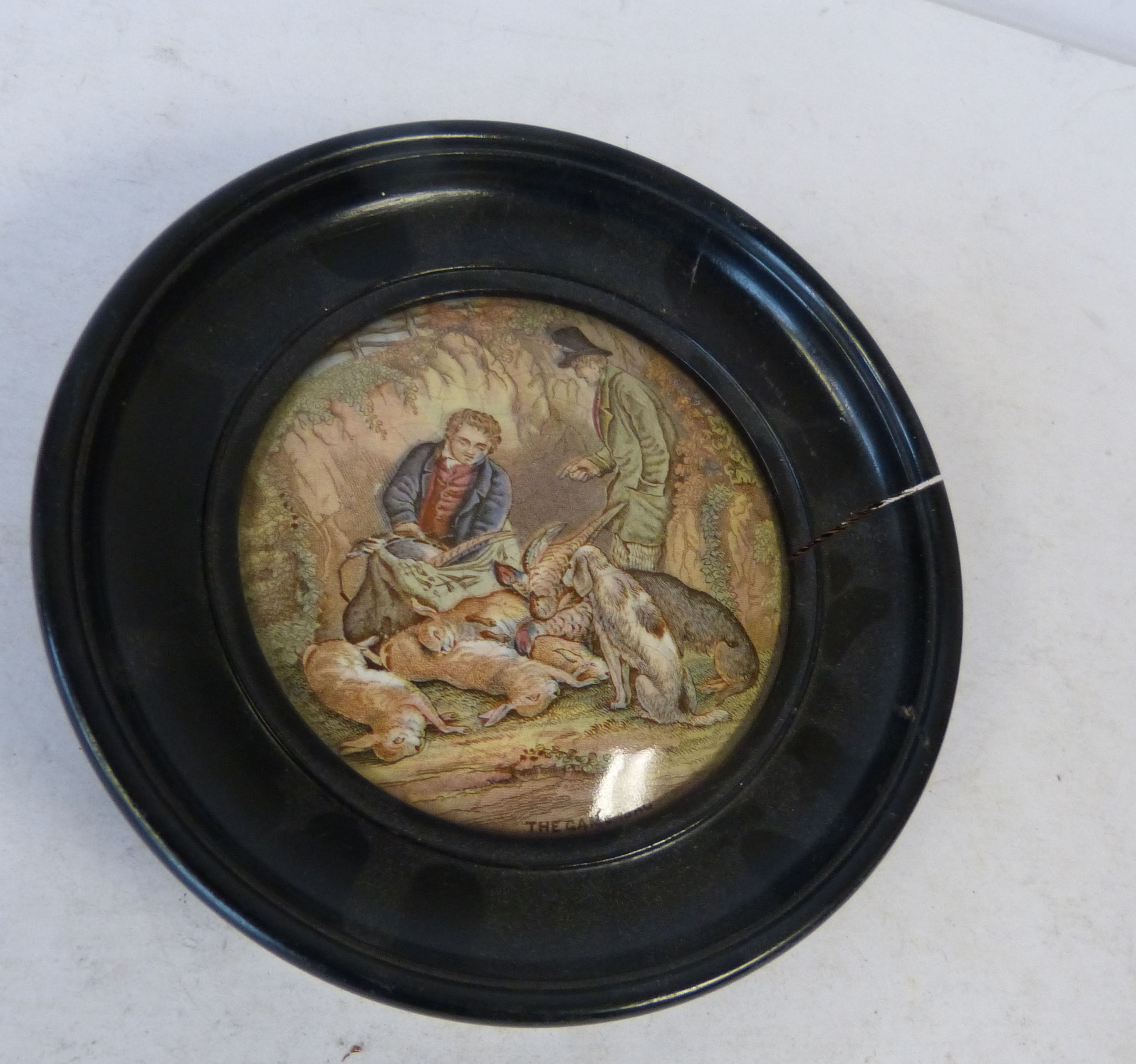 A 19th Century Round Pot Lid ``A Game Bag`` in ebonised frame, 16cm diameter overall