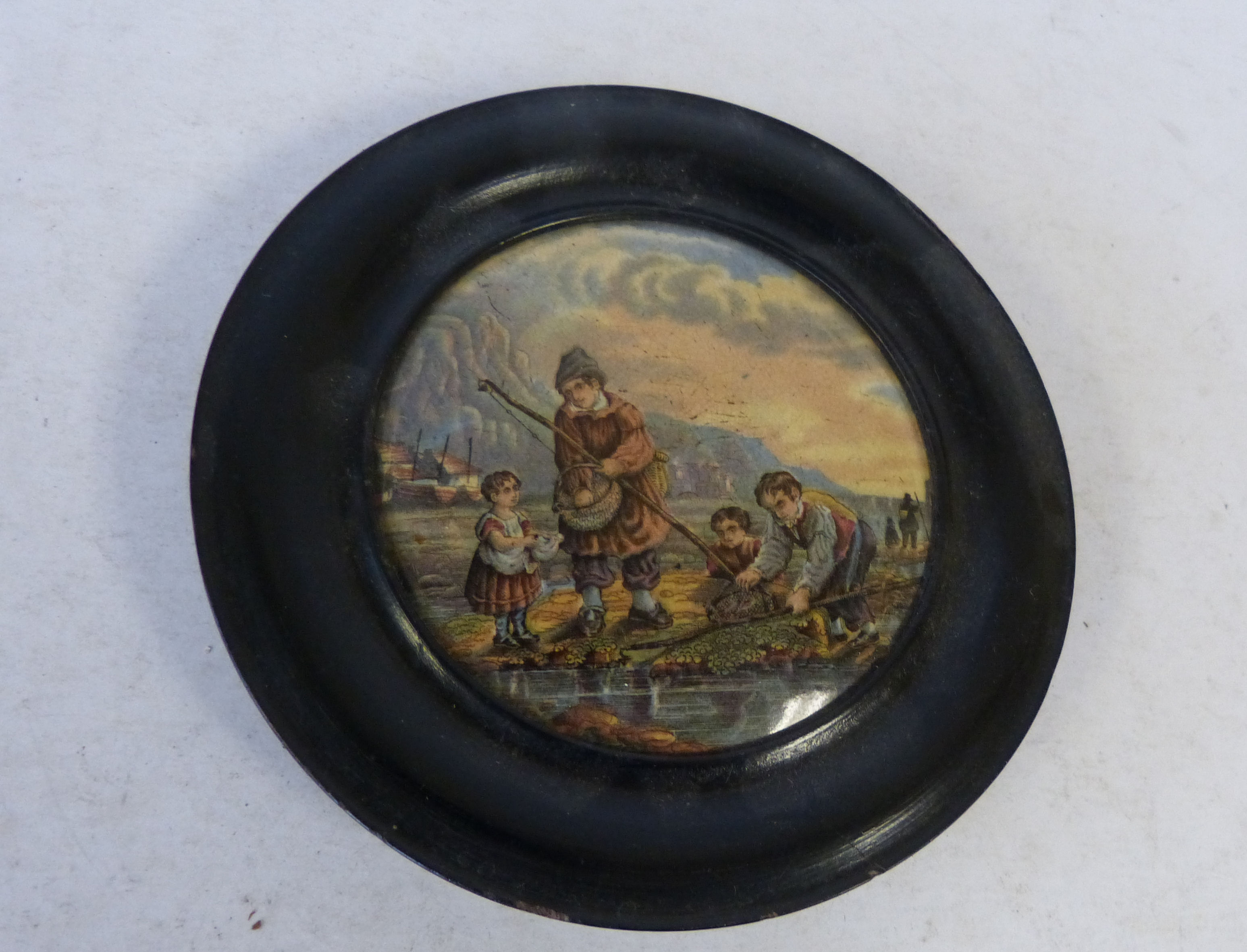 A 19th Century Round Pot Lid depicting young figures fishing, in ebonised frame