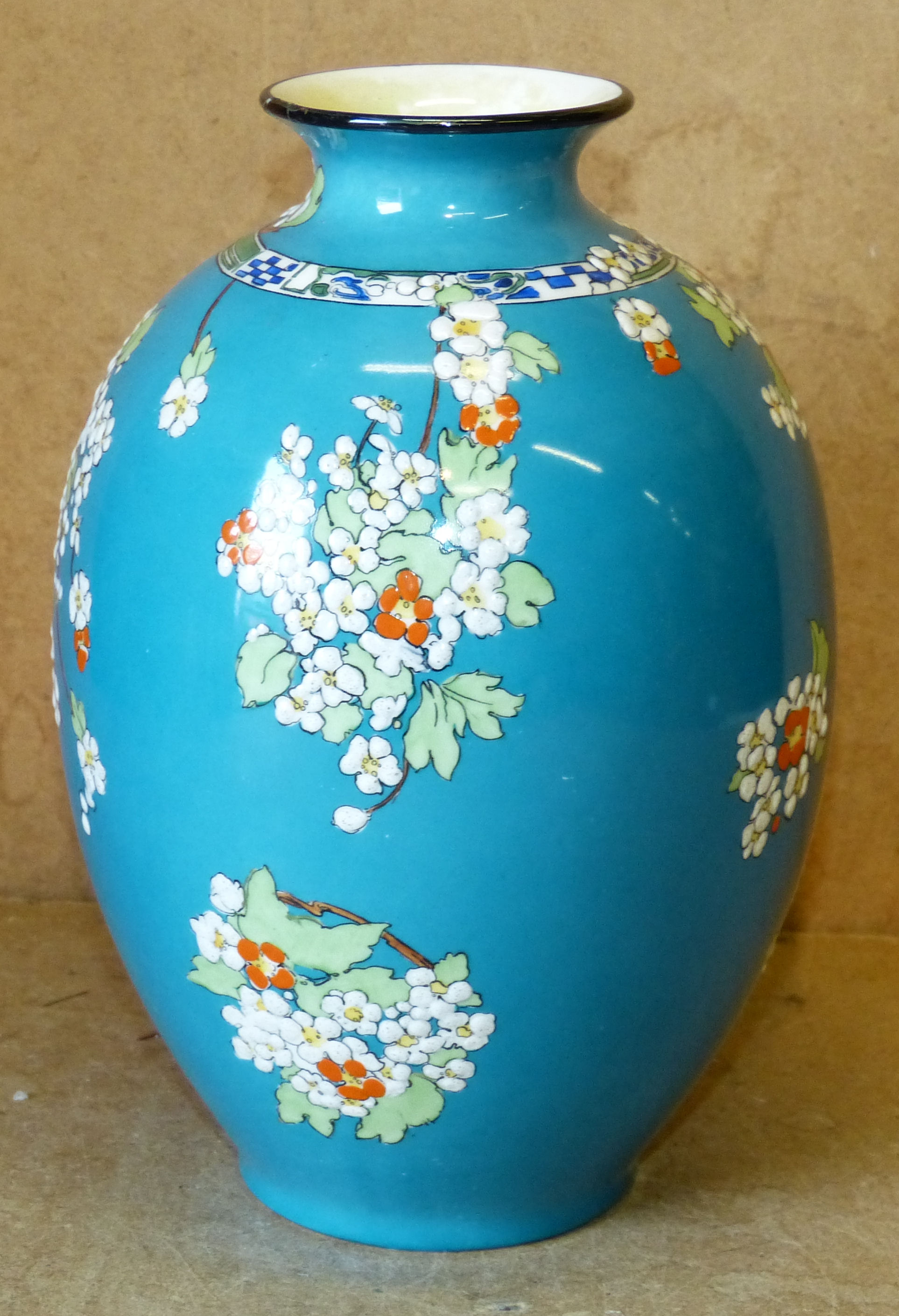 A Royal Doulton Bulbous Thin Necked Trumpet Shaped Vase on turquoise ground having raised multicoloured floral