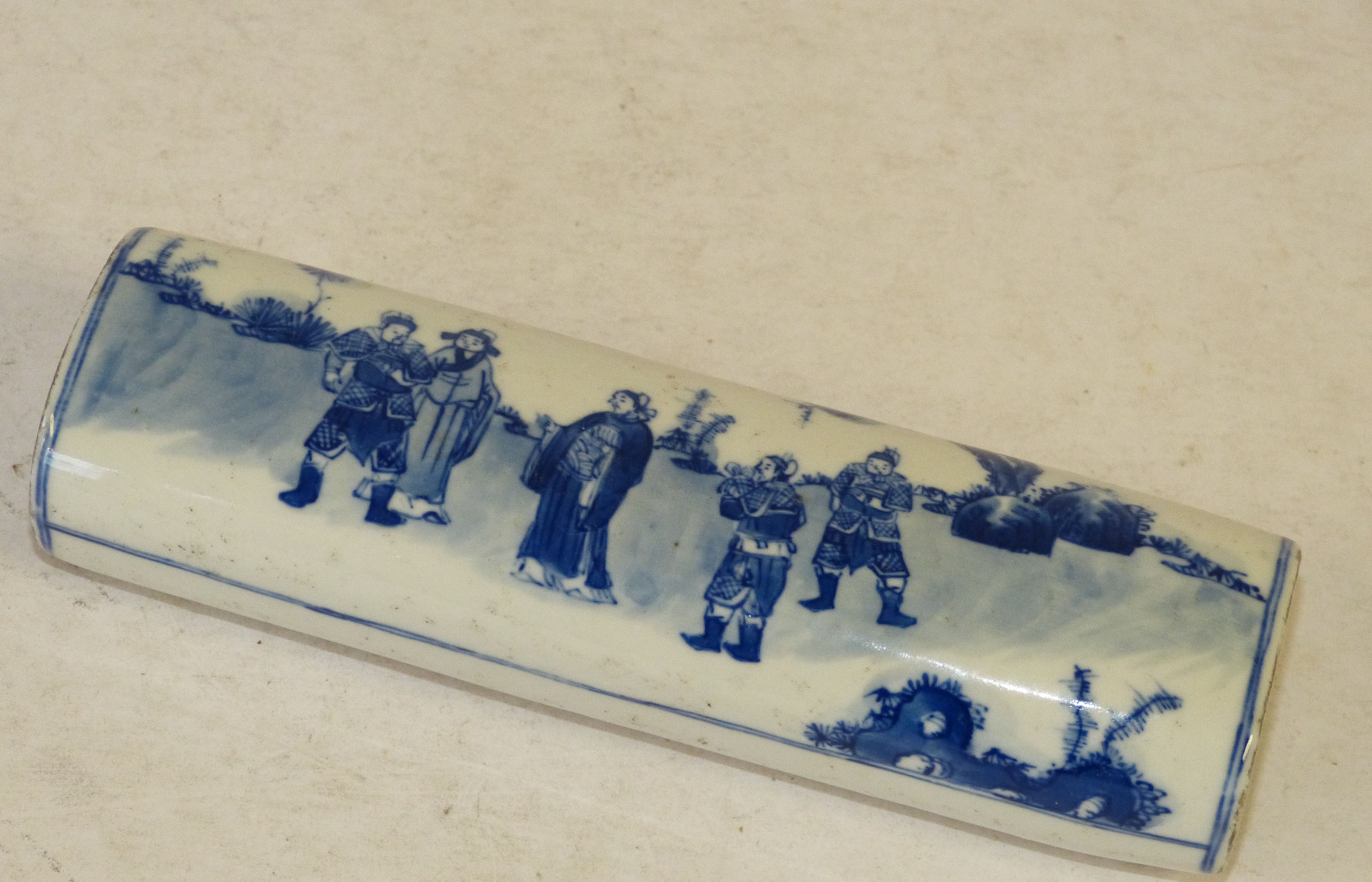 An Oriental Paperweight on blue and white ground depicting warriors, 16cm long