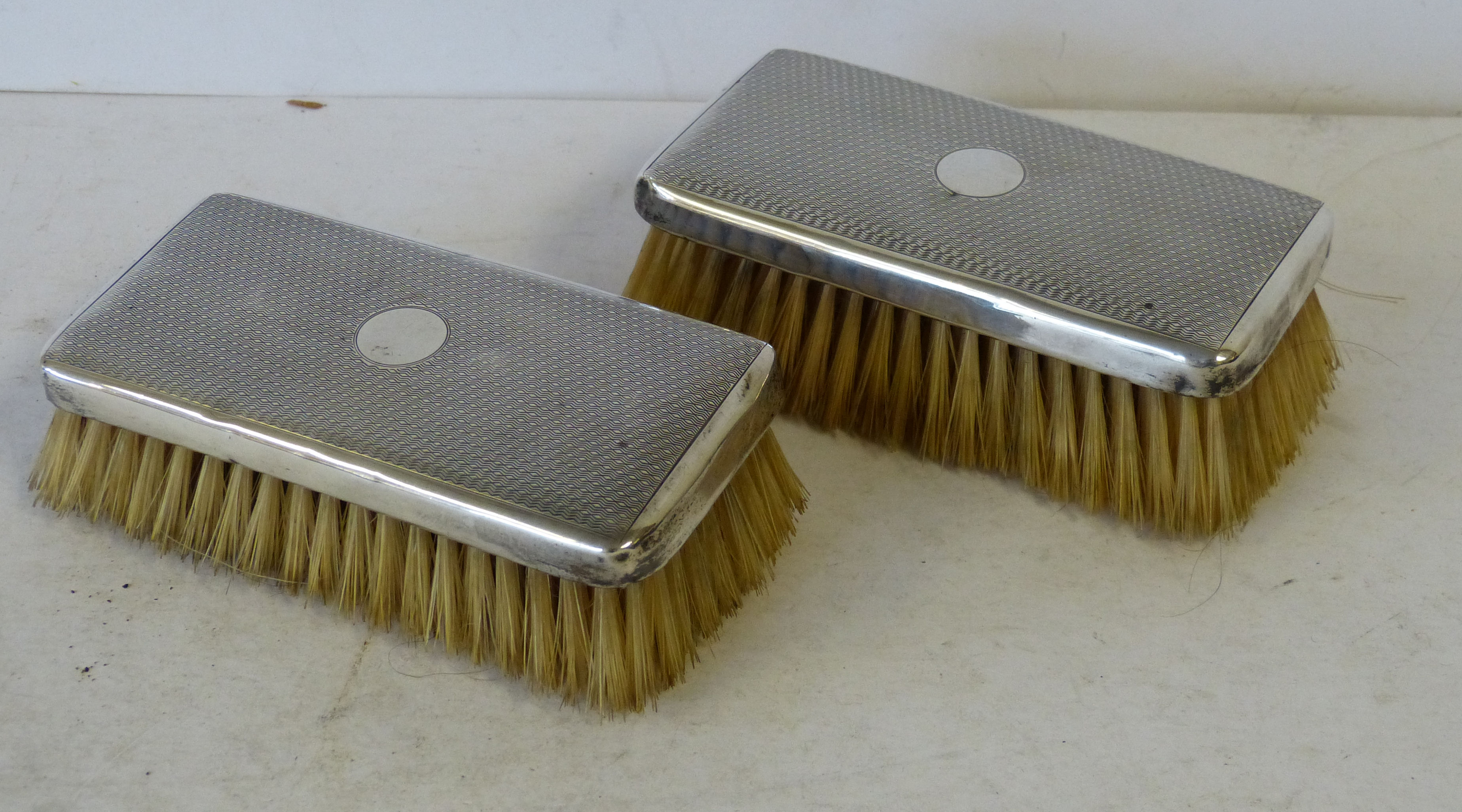 A Pair of Birmingham Silver Mounted Gentlemen`s Hairbrushes having engine turned decoration