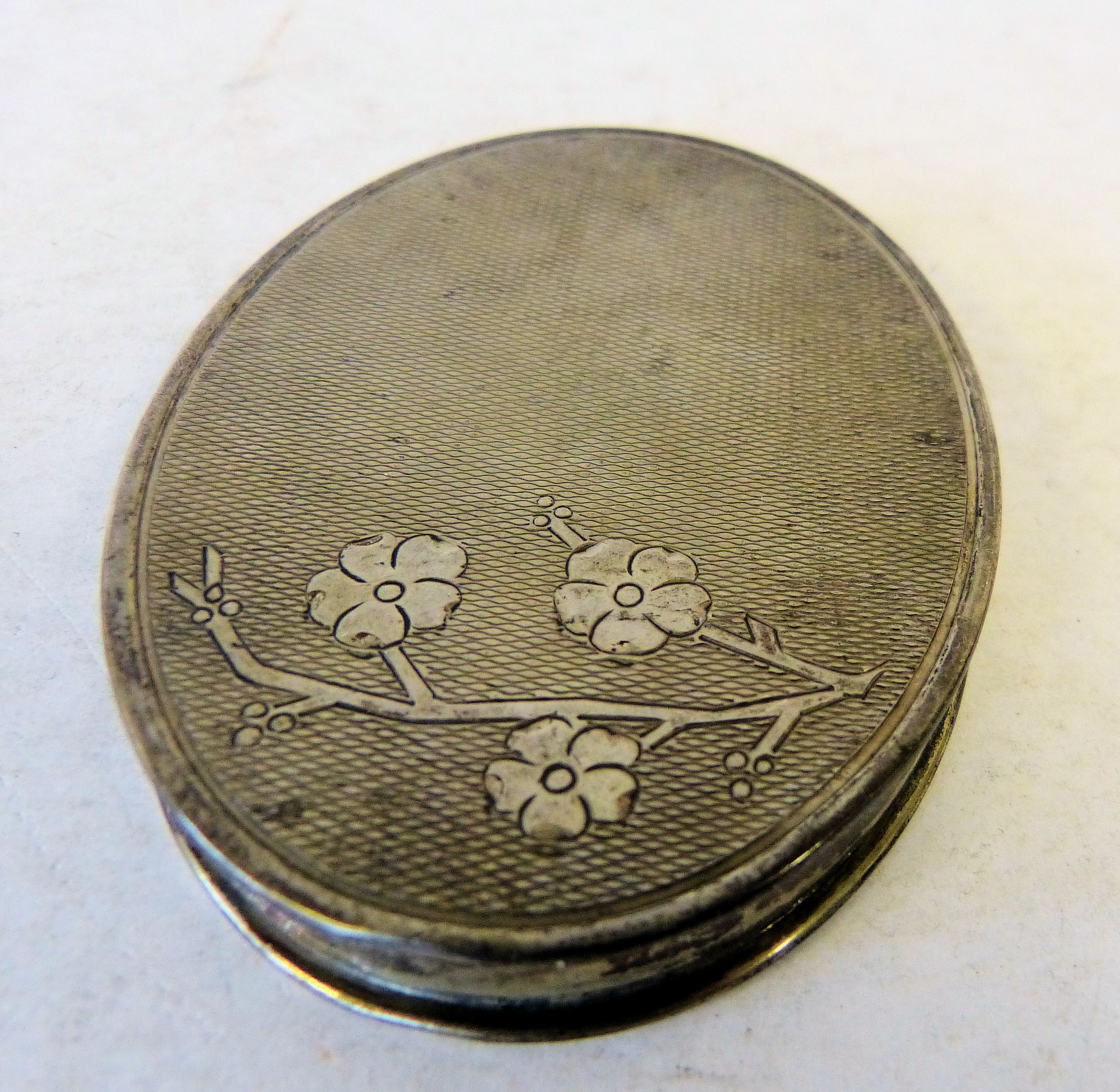 A Continental Silver Coloured Metal Flat Oval Snuff Box having engine turned hinge lid