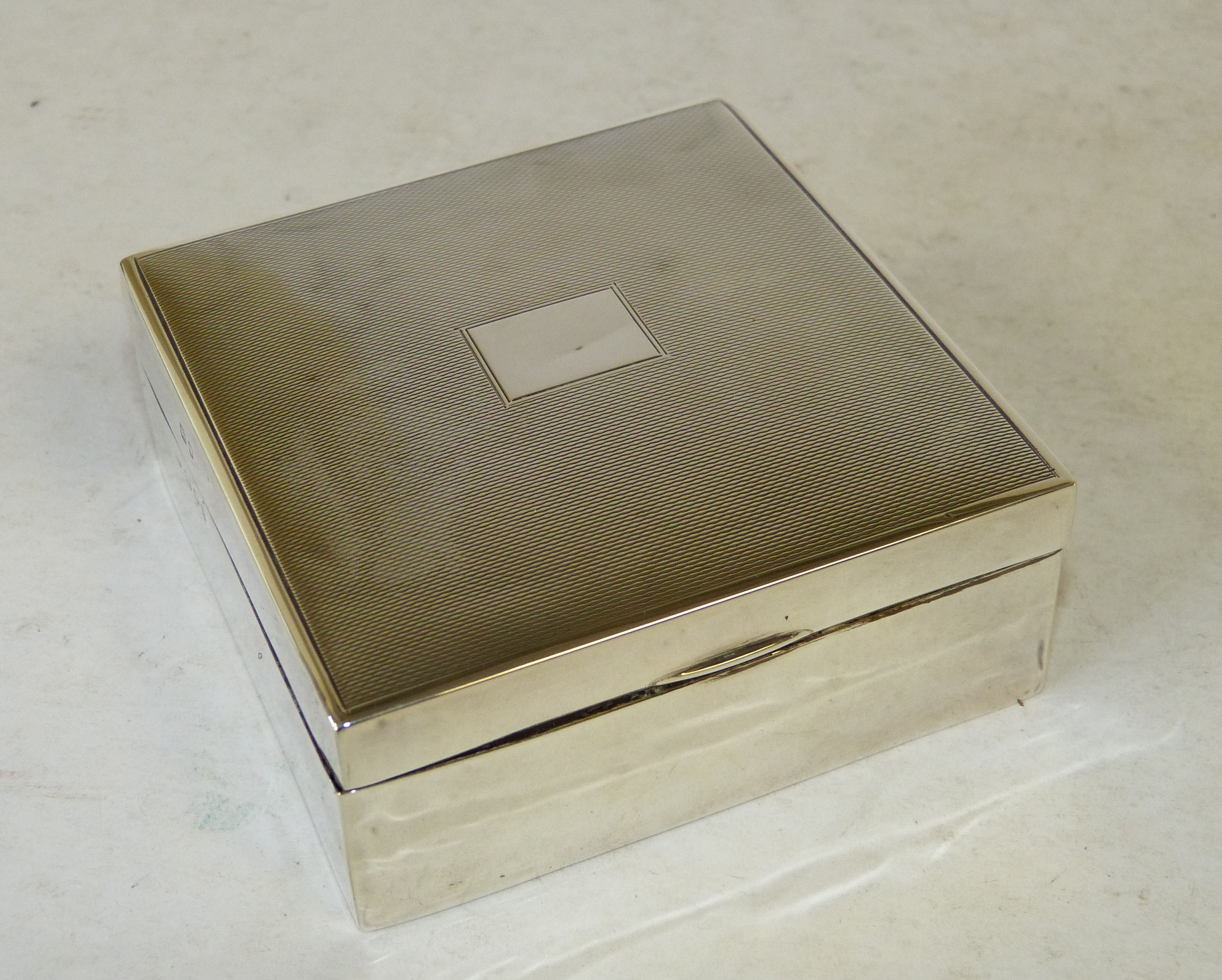 A London Silver Mounted Square Cigarette Box having hinged engine turned lid