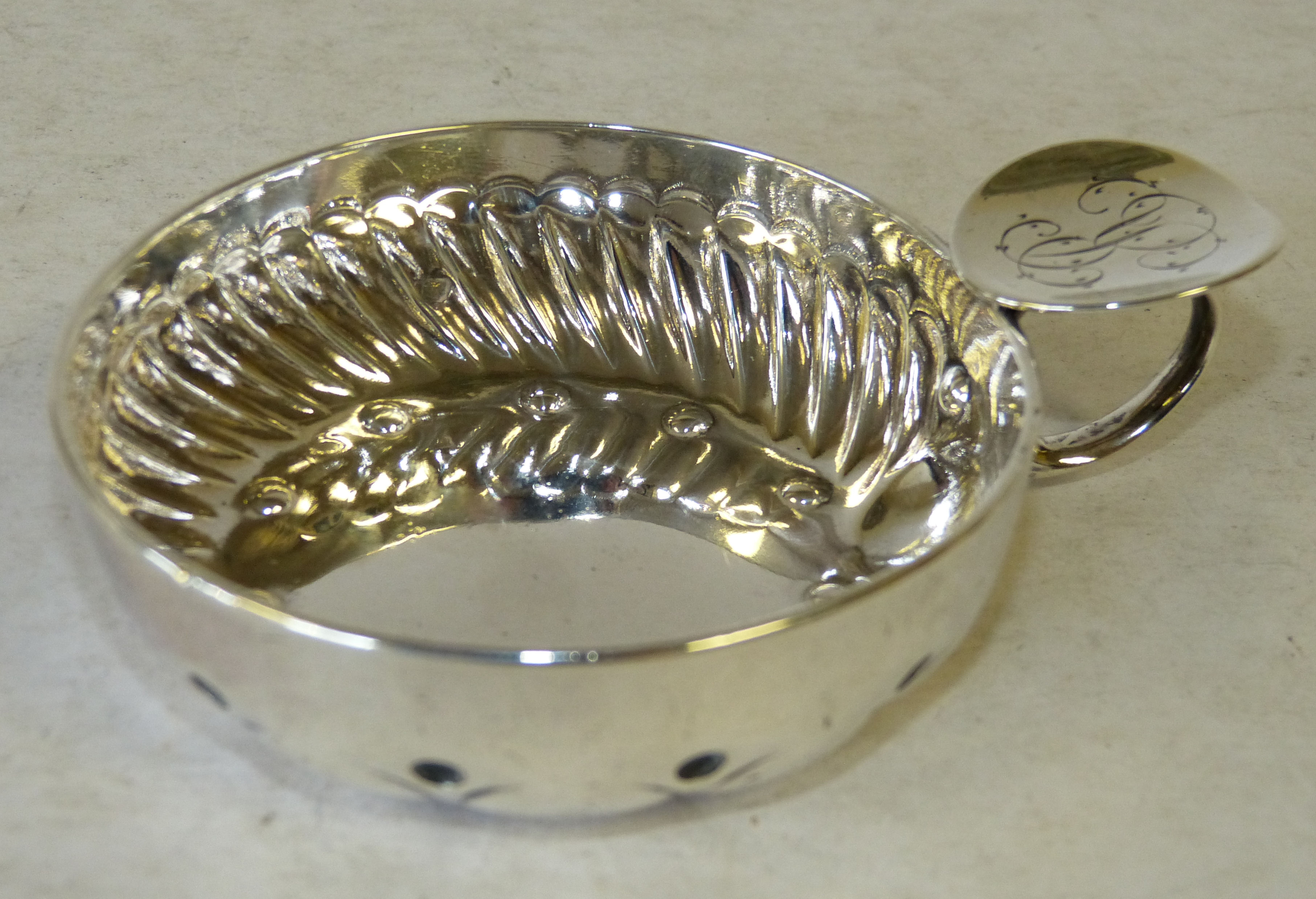 A Silver Coloured Metal Wine Taster having embossed decoration