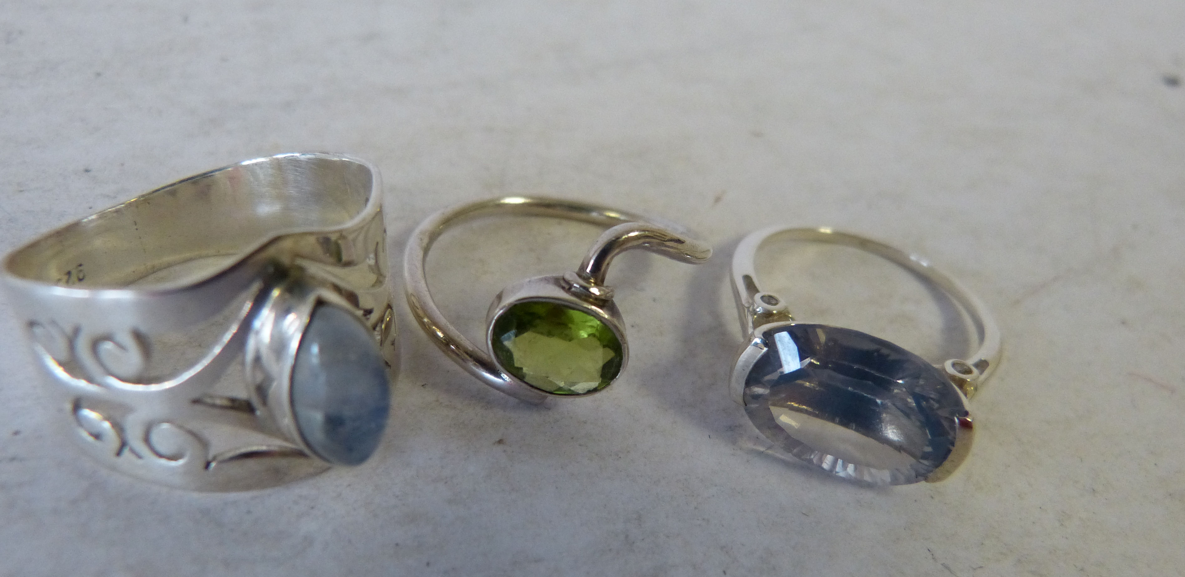 A Silver Ring Set with Eclipse Quartz, another similar ring and a silver ring set with Peridot