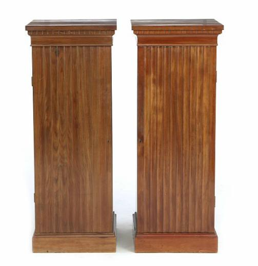 A pair of empire style mahogany pedestal cupboards