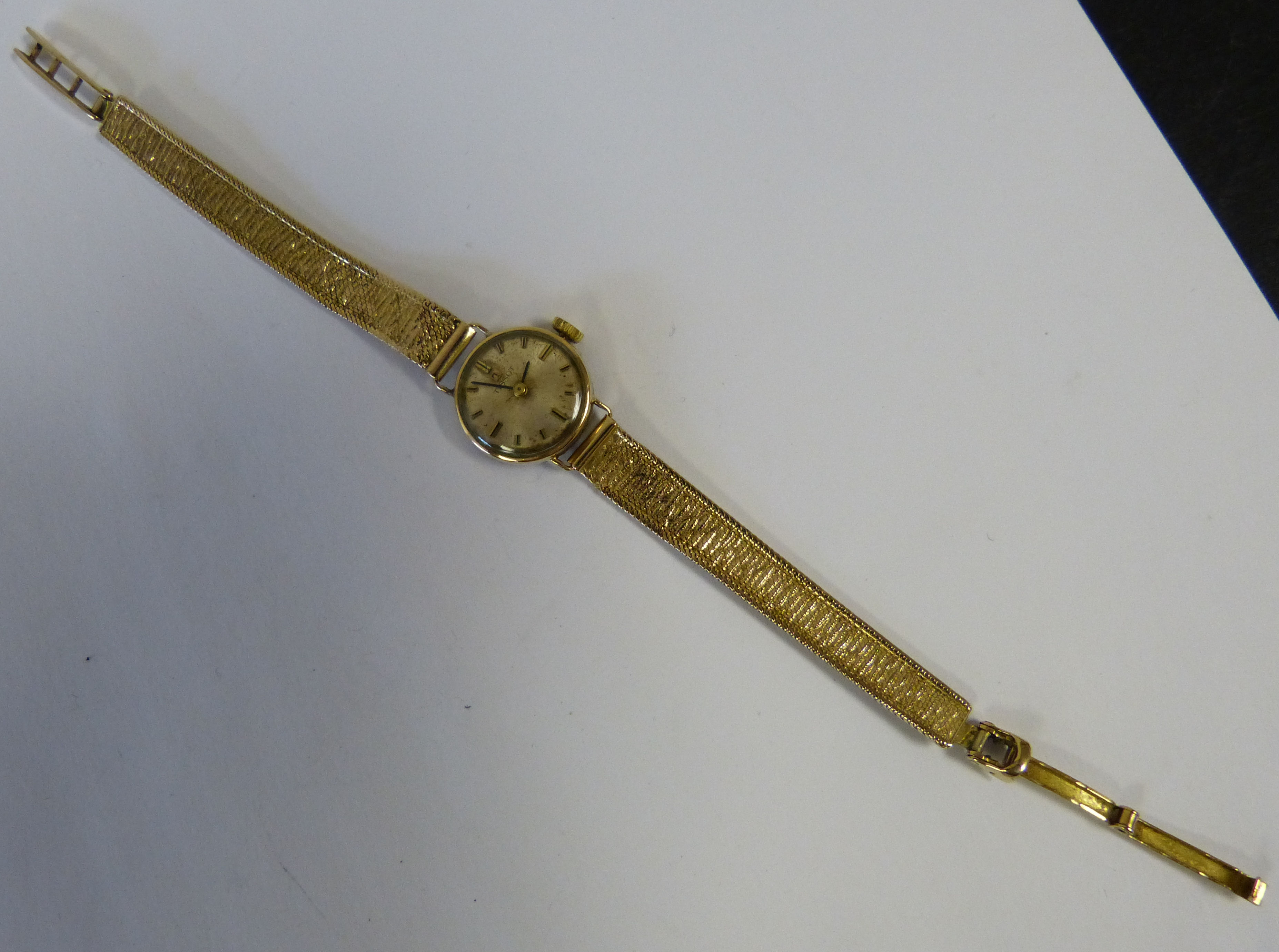 A 9ct Gold Tissot Ladies Circular Wristwatch having matching strap bracelet, weighable gold 12.2grms