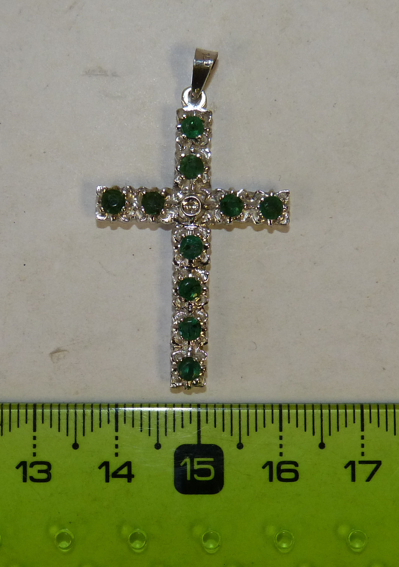 An 18ct White Gold Cross Pendant mounted with emeralds and small diamond, 4.6 grams gross