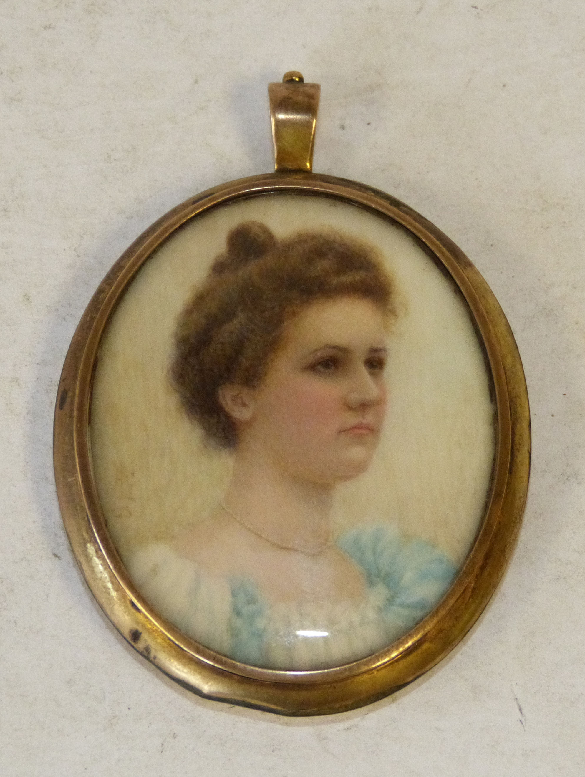 An Oval Miniature shoulder length portrait of a young lady wearing pearls, mounted as a pendant