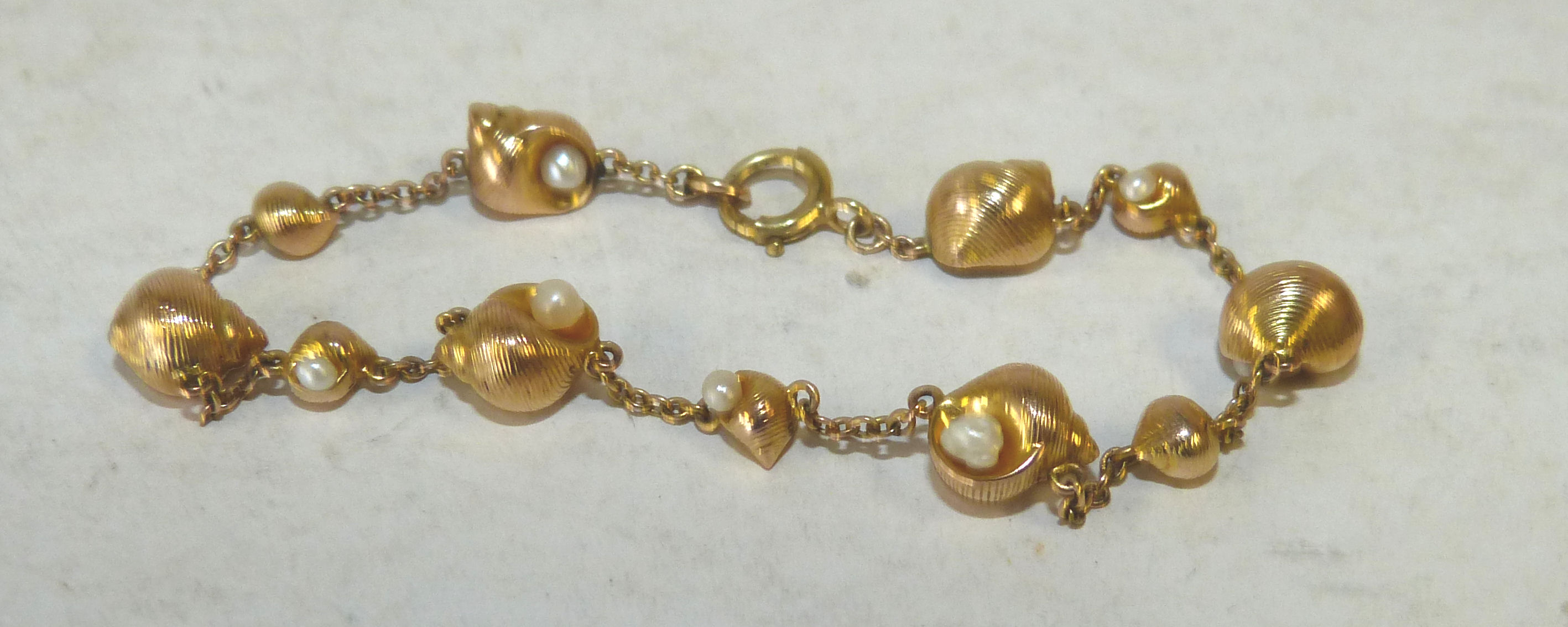 A Gold Linked Bracelet interspersed by shell with pearls (1 pearl missing) 6gms gross