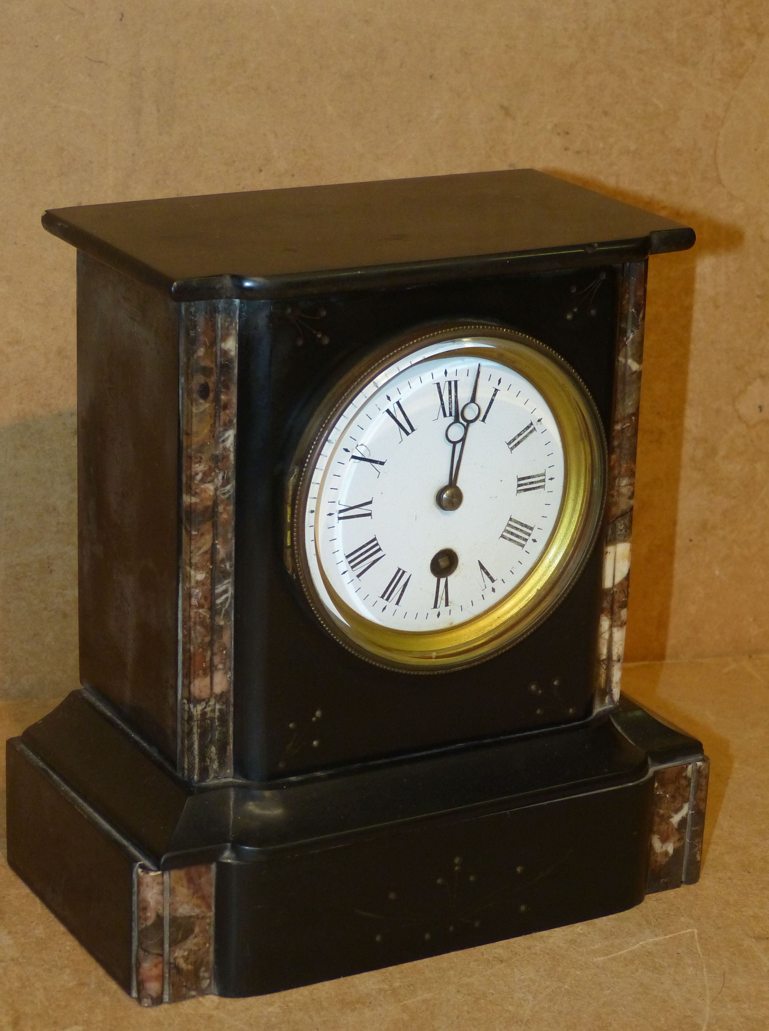 A Black Slate Mantle Clock having circular white enamel dial with Roman numerals