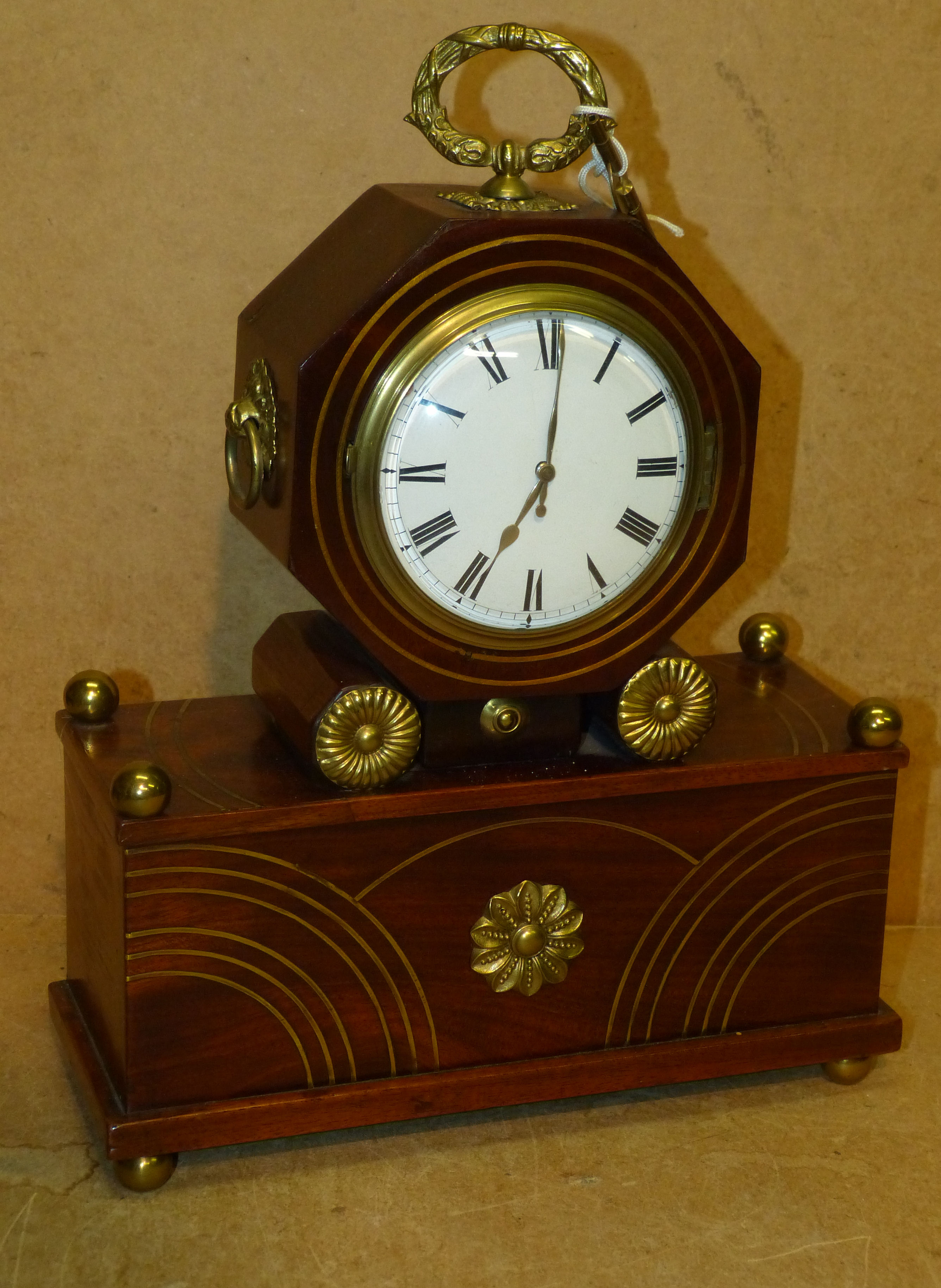 A Mahogany Regency Style Timepiece having all over inlaid brass stringing, circular white enamel dial with carrying handle on ba