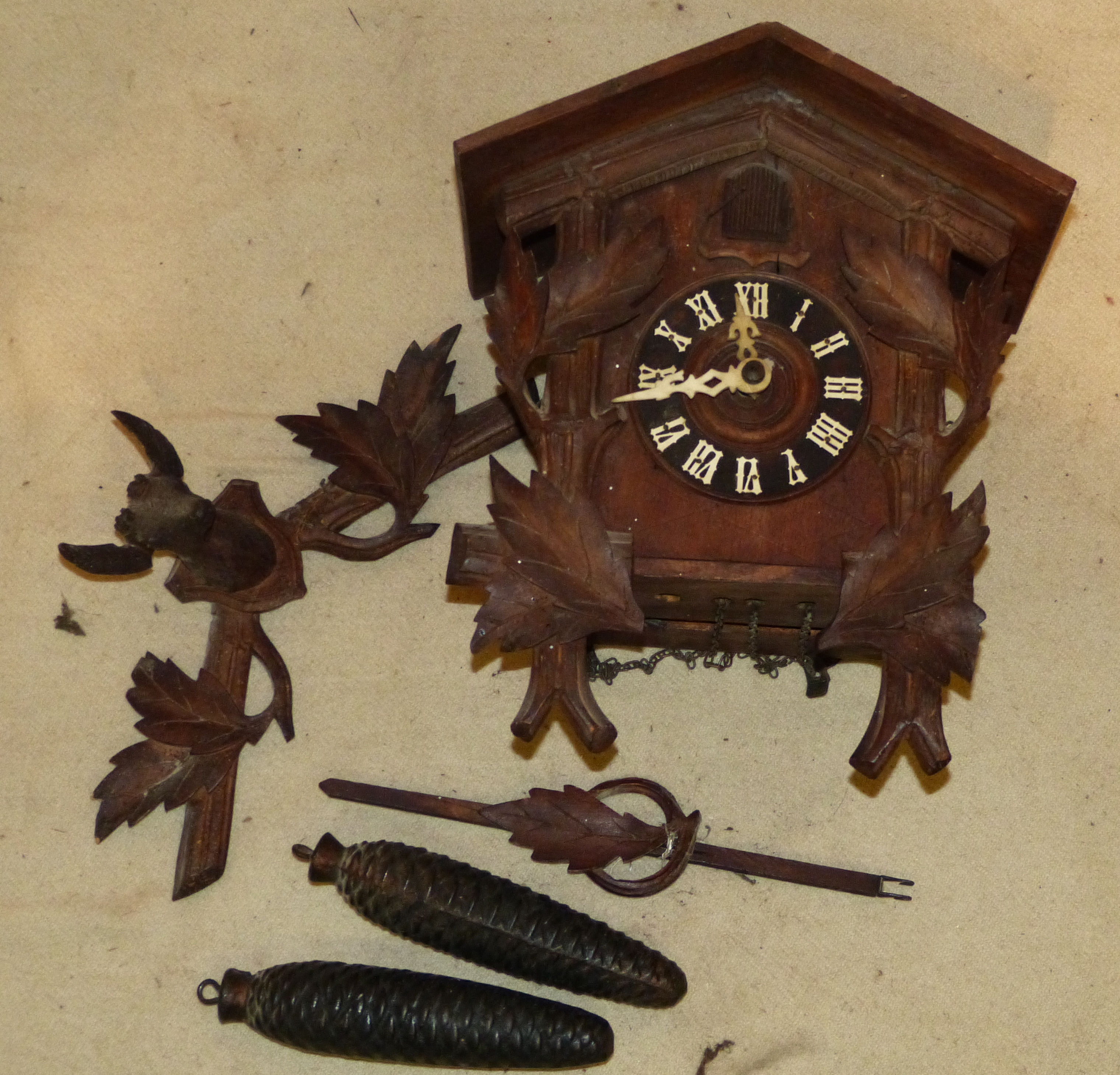 A Continental Cuckoo Clock having carved deer motif to top with all over leaf decoration, with weights