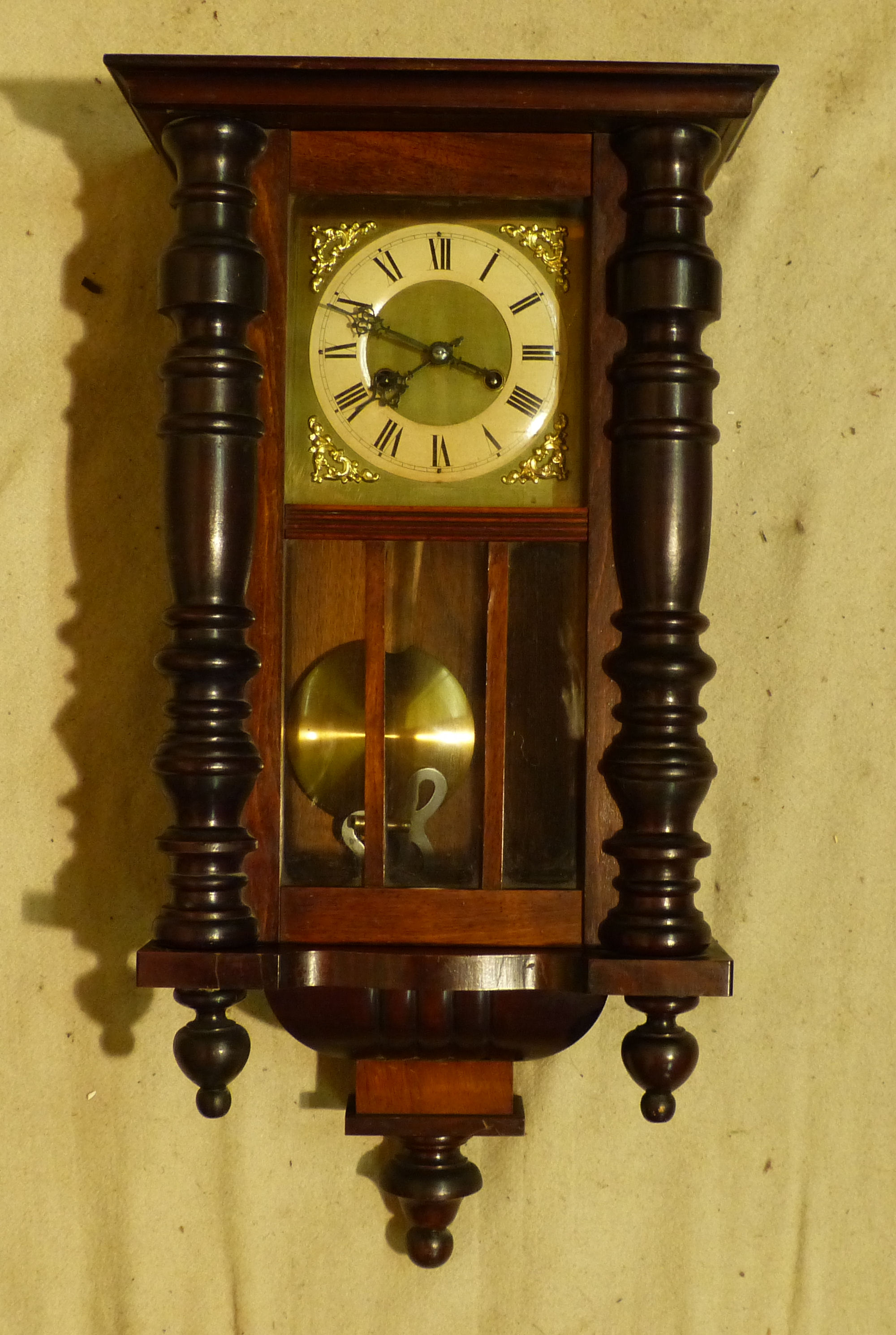 A Walnut Hanging 8 Day Striking Wall Clock having half round column supports, square gilt dial with Roman numerals