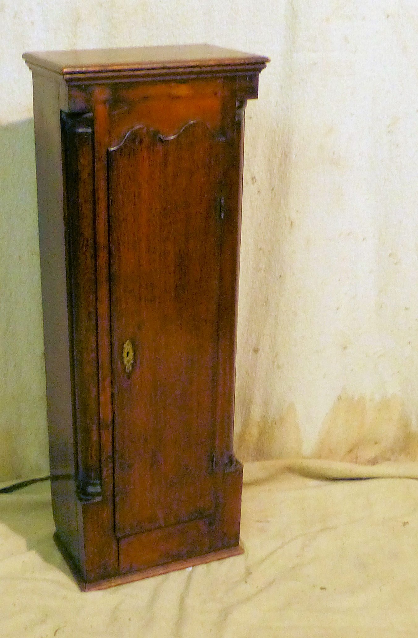 A 19th Century Oak Clock Case Trunk having scalloped panel door with half round supports