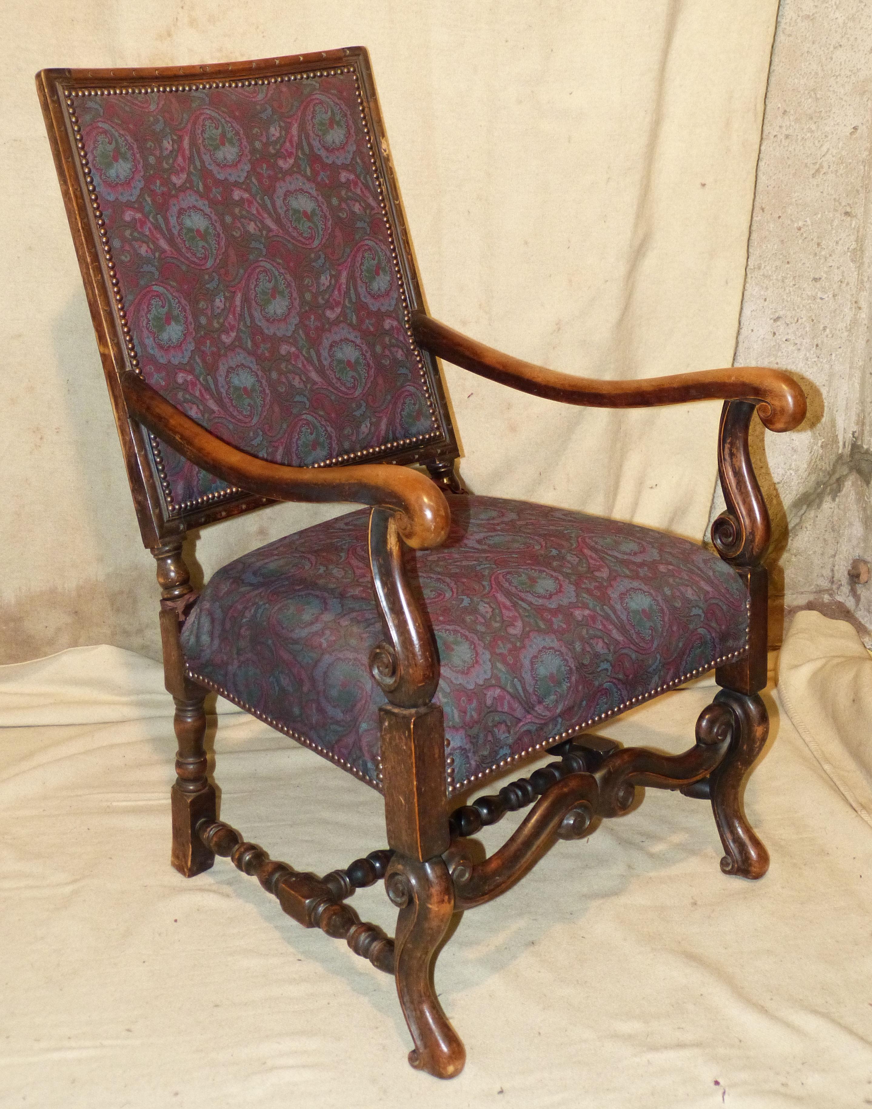 A Walnut Armchair having overstuffed seat and backs