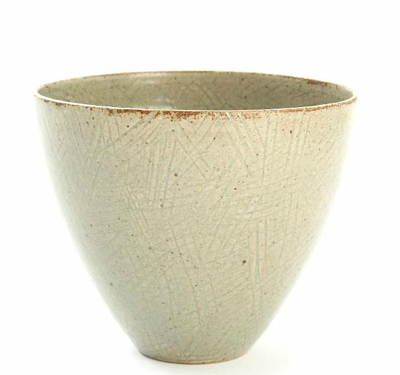 A stoneware bowl, decorated with speckled gray glaze and incised with patterns
