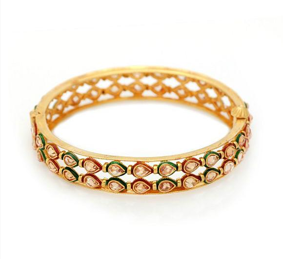 An Indian bangle set with numerous fancy-cut cubic zirconia, red and green enamel, mounted in 21k gold