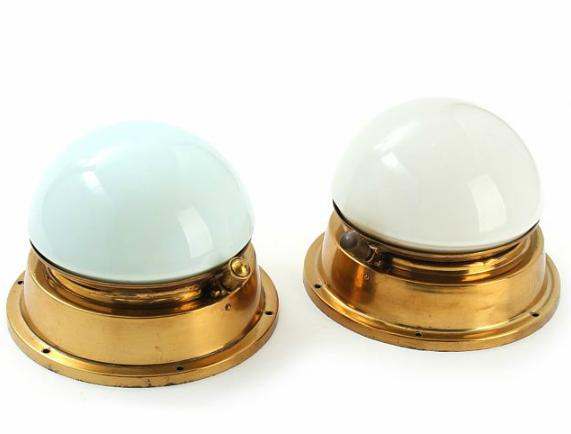 A pair of almost identical German brass and white glass wall lamps