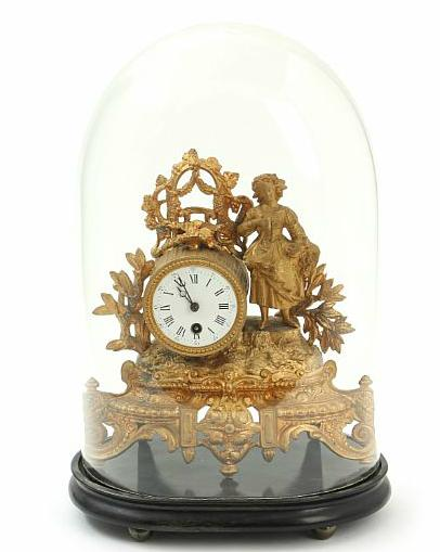 A late 19th century French bronzed mantel clock decorated with a young lady holding a nestling