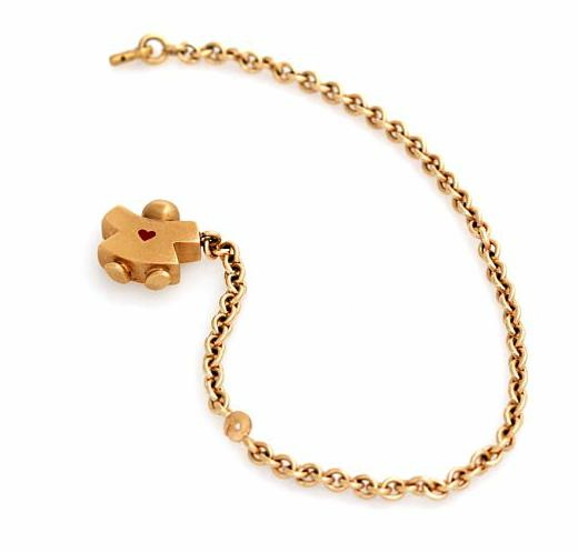 A bracelet of 14k gold with charm in shape of a girl set with a red enamel heart