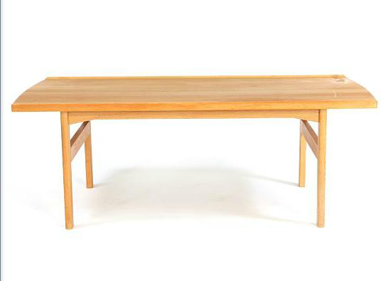A solid oak coffee table, slightly concave sides, rail with inlays of lighter wood