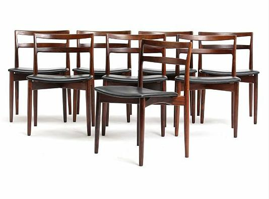 Eight Brazilian rosewood side chairs. Seats upholstered with black leather