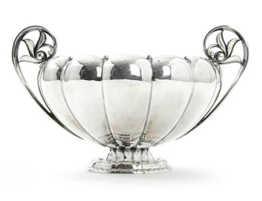 A sterling silver sugar bowl decorated with stylized foliage and silver beading.