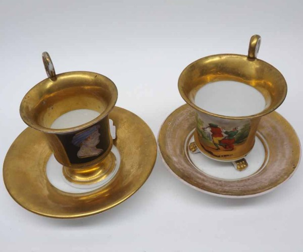Two 19th century continental gilt decorated cups and saucers, the cups both with panels of classical figures, wear throughout