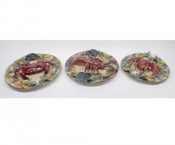 """Three 20th century Portuguese Majolica style plates, one decorated with a lobster, the others with crabs, largest 13"""" diameter"""