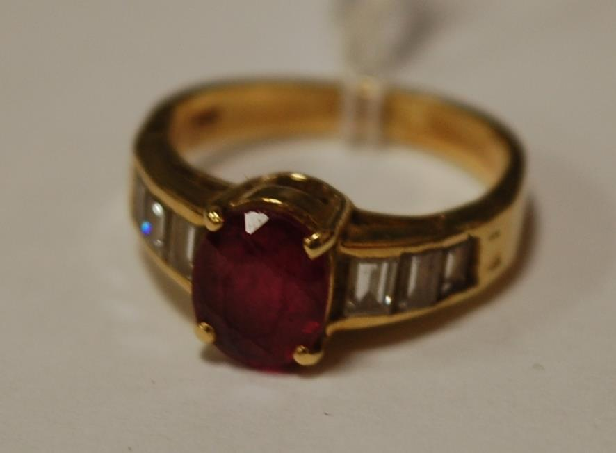 A modern ladies 18ct gold oval cut ruby dress ring