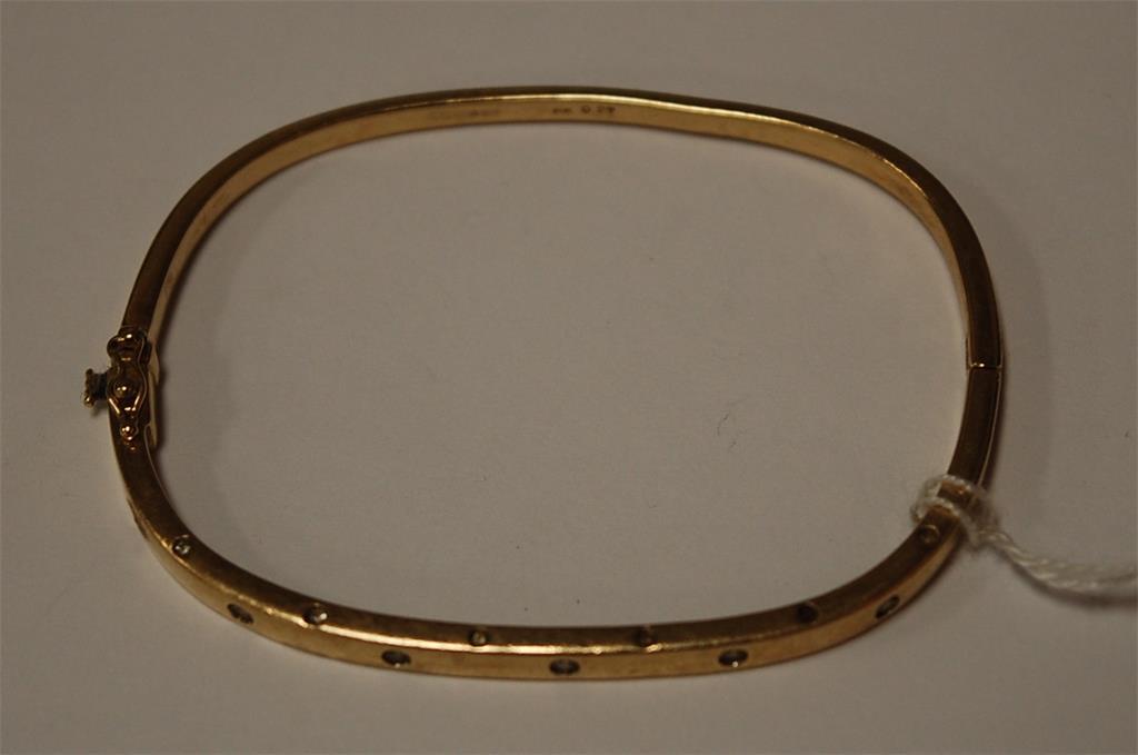 After Chanel - a 9ct gold diamond set hinged bangle, 14g