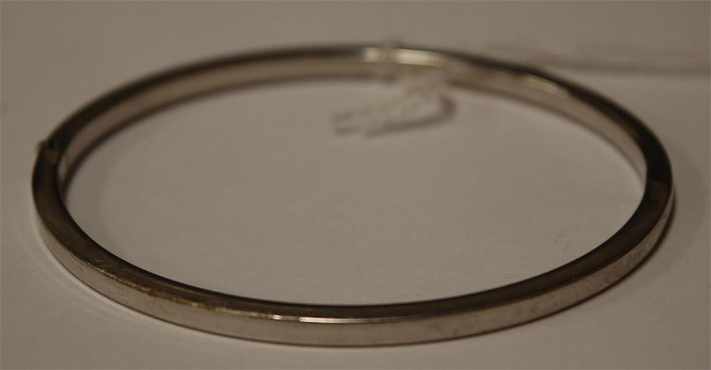 After Chanel - a 9ct white gold and diamond set hinged bangle, 6.5g
