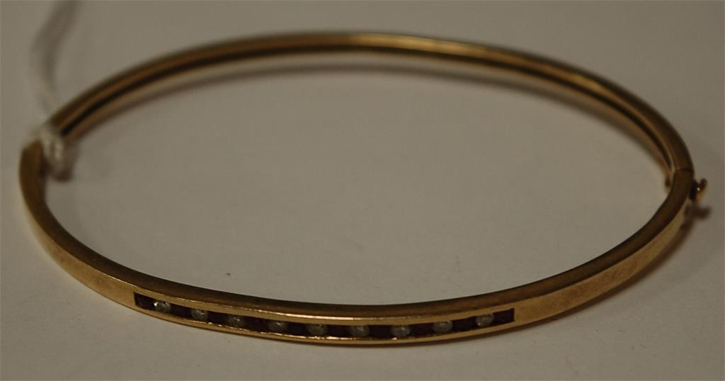A 10ct gold ruby and diamond channel set hinged bangle