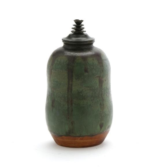 A small stoneware lid jar decorated with green and brown glaze with some blue elements