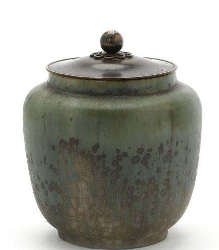 A stoneware lid jar decorated with green and blue glaze with greyish brown elements