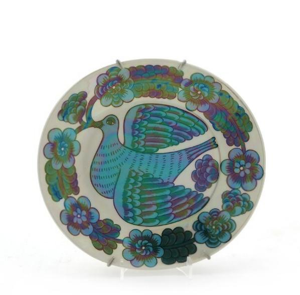 A small oval faience dish decorated with bird and flowers in blue and green glaze, iredescent surface
