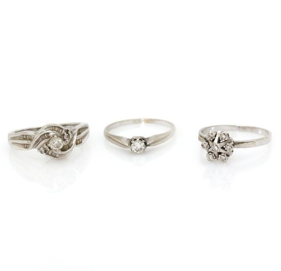 Three diamond rings respectively set with single-, brilliant- and baguette-cut diamonds