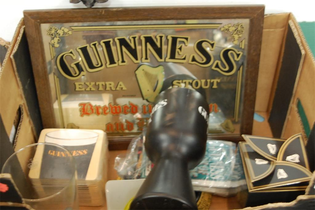 A box of assorted Guinness memorabilia to include wall mirror, beer mats, and pint glass etc