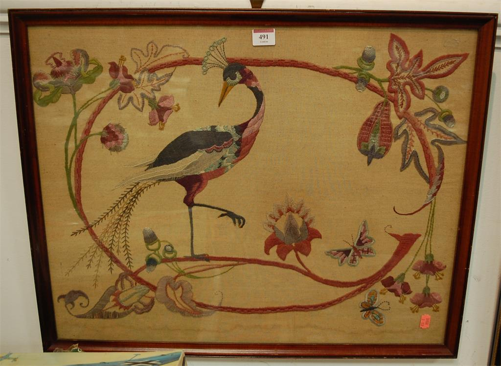 An early 20th century needlework embroidered panel depicting a peacock amongst foliage