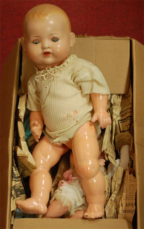 A mid 20th century German doll with flirty eyes and jointed composition body