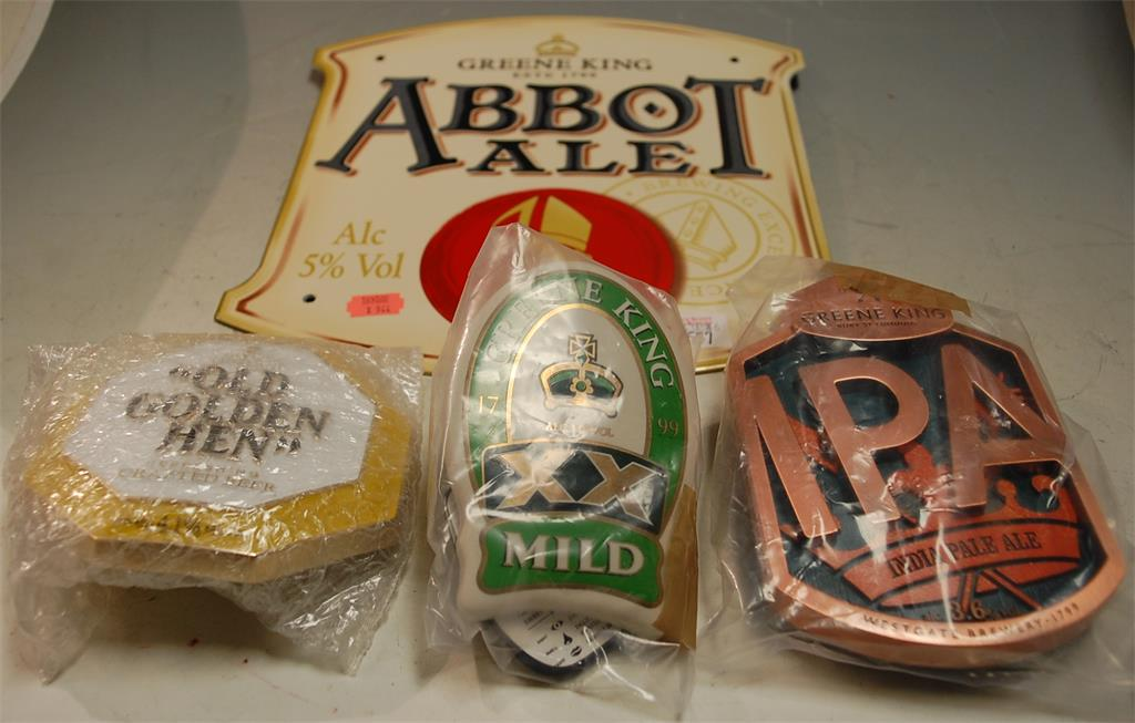 A reproduction Greene King enamel Abbot Ale sign together with various Greene King beer pump clips