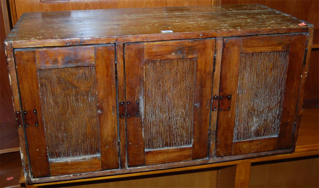 A stained pine three drawer cupboard