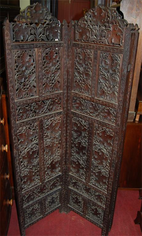 An Eastern carved and pierced teak four section dressing screen