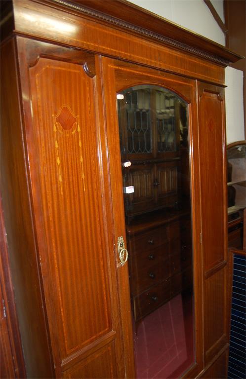 An Edwardian mahogany and satinwood strung single mirror door wardrobe