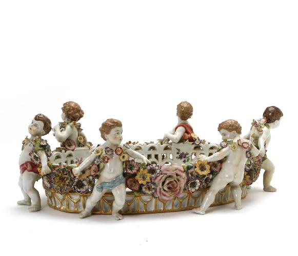 A large German porcelain jardiniere, decorated in colours and gold, pierced sides adorned with repoussé flowers and modeled cupi
