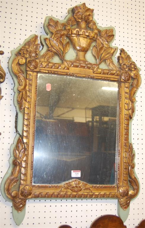 A 19th century French floral relief carved wall mirror, gilt decorated with urn surmount