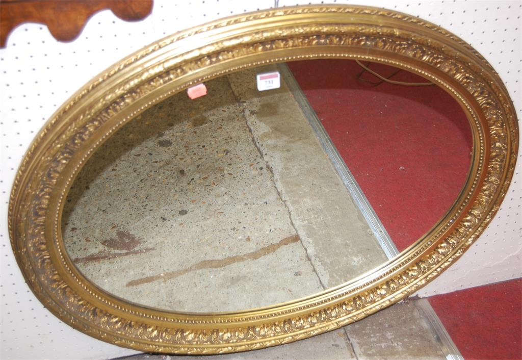 A gilt and floral decorated oval wall mirror
