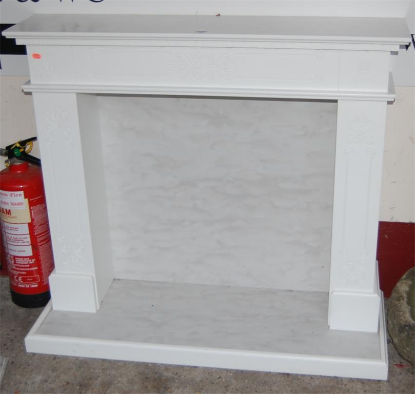 A modern white painted integral fire surround